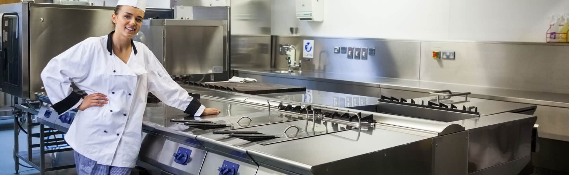 lady in chef uniform standing in a commercial kitchen